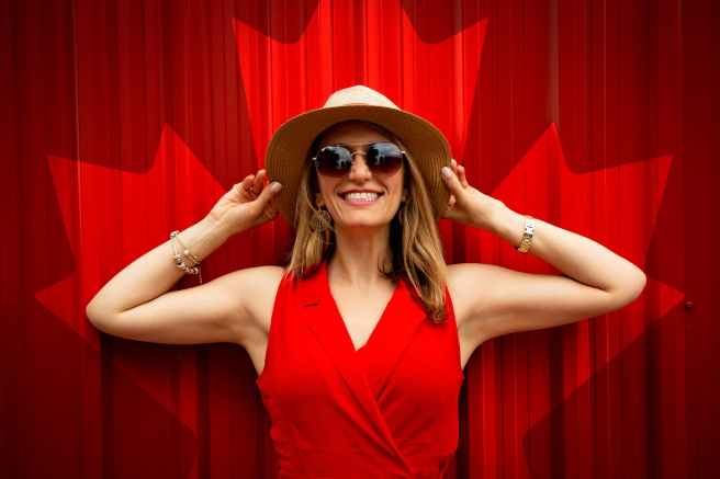 woman in red sleeveless dress with canada flag printed background